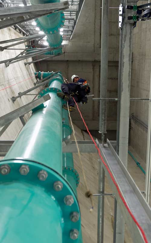 working at height with ropes desecning a large pipe